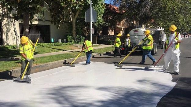 Рабочие применяют светоотражающий герметик на улице в душном Лос-Анджелесе.